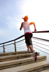 fitness woman running at stone stairs to mountain peak