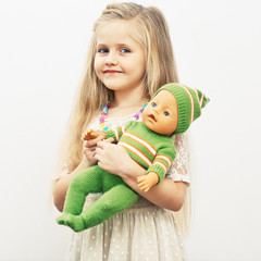 Girl play with baby doll. Mothers day concept.