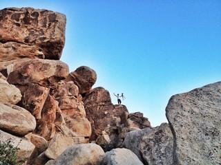 Fotograf mit ausgebreiteten Armen auf Steinen