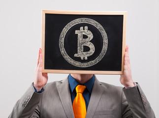 Businessman hiding his face behind bitcoin symbol