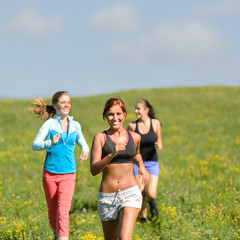 Friends enjoy running through sunny meadow