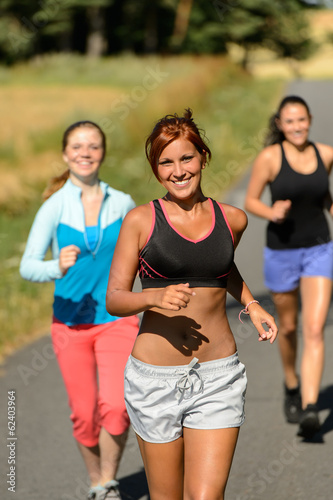 Friends jogging together outdoors sunny path
