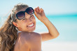 Portrait of happy young woman in sunglasses on beach