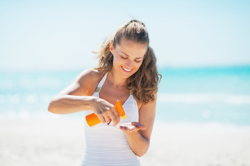 Happy young woman on beach applying sun screen creme