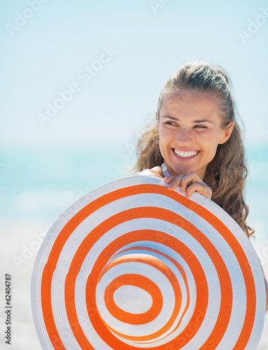 Portrait of smiling young woman with hat on beach