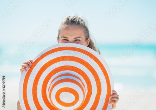 Young woman hiding behind hat on beach