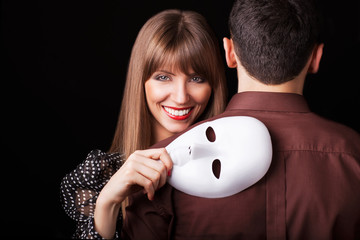 Fashion Happy Couple in Love holding a white mask face.