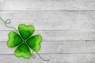 Four leaved clover on wooden background