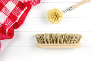 top-view of dish-washing brush and scrubbing brush and tea towel