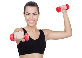 Happy fitness woman lifting dumbbells smiling.