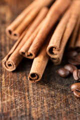 Coffee and cinnamon sticks on grunge wooden background