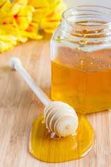 honey dipper on a background of a jar with honey