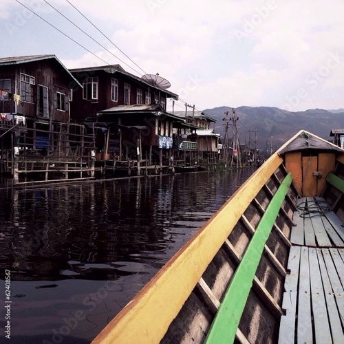 boat floating through a village on Inle Lake in Myanmar