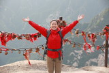 woman hiker open arms at peak of mountain huashan