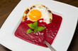 Beetroot cream soup with fried egg and bacon