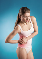Young woman with pancreas pain over blue background