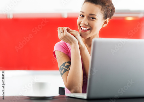 Smiling african american woman with laptop