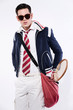 Retro tennis fashion man with sunglasses holding a red bag with