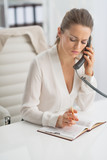 Modern business woman talking phone and writing in notepad