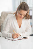 Modern business woman writing in notepad