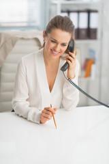 Portrait of happy modern business woman talking phone in office