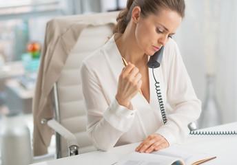 Modern business woman talking phone in office