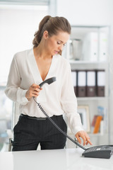 Modern business woman dialing phone