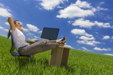 Woman Relaxing at Office Desk in Green Field