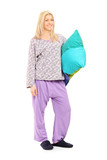 Blond girl in pajamas holding a pillow