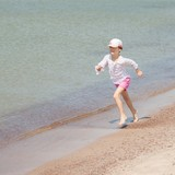 Happy girl runs along the seashore