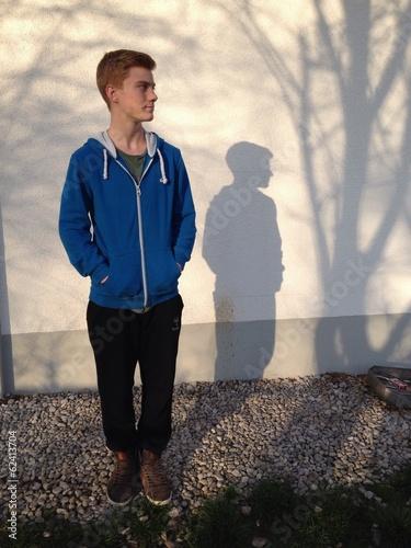 Teenager vor Wand mit Baum