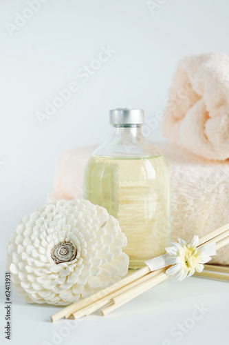Sandal oil in a bottle and towels for spa procedures
