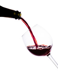 Red wine pouring into wine glass. isolated on white