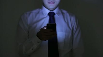 暗闇の中でスマートフォンを見る男性