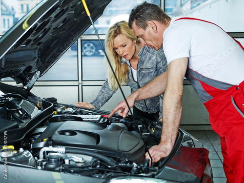 Car mechanic explains something to a customer