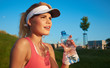 fitness and lifestyle concept - woman drinking water after doing