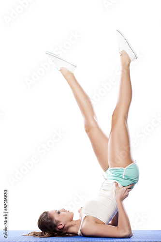 Portrait of young girl doing a yoga pose with feet in the air