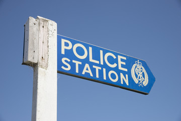 Wooden sign post pointing towards Police Station