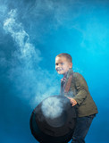 Adorable boy posing in cloud of steam, close-up