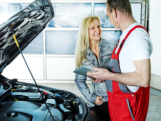 Customer and mechanic in a garage look at a quotation