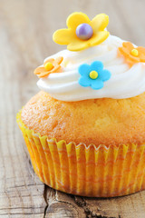 Cupcake decorated with colourful flowers and buttercream