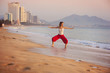 Sport woman doing exercise at the city beach.