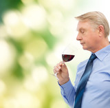 elderly man smelling red wine