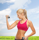 young sporty woman with light dumbbells outdoors