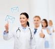 smiling female doctor pointing to envelope