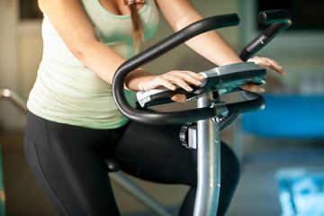 shot of sporty woman riding exercise bike at fitness club
