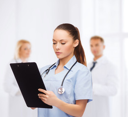serious female doctor or nurse with stethoscope