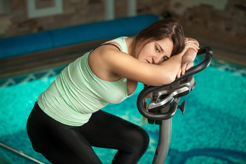 brunette woman relaxing after training on exercise bike