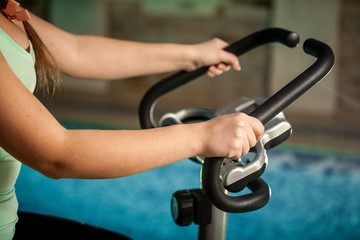 Closeup shot of woman holding steering heel on bike trainer