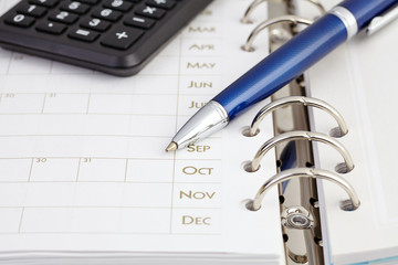 Calculator and ball pen on organizer. Selective focus
